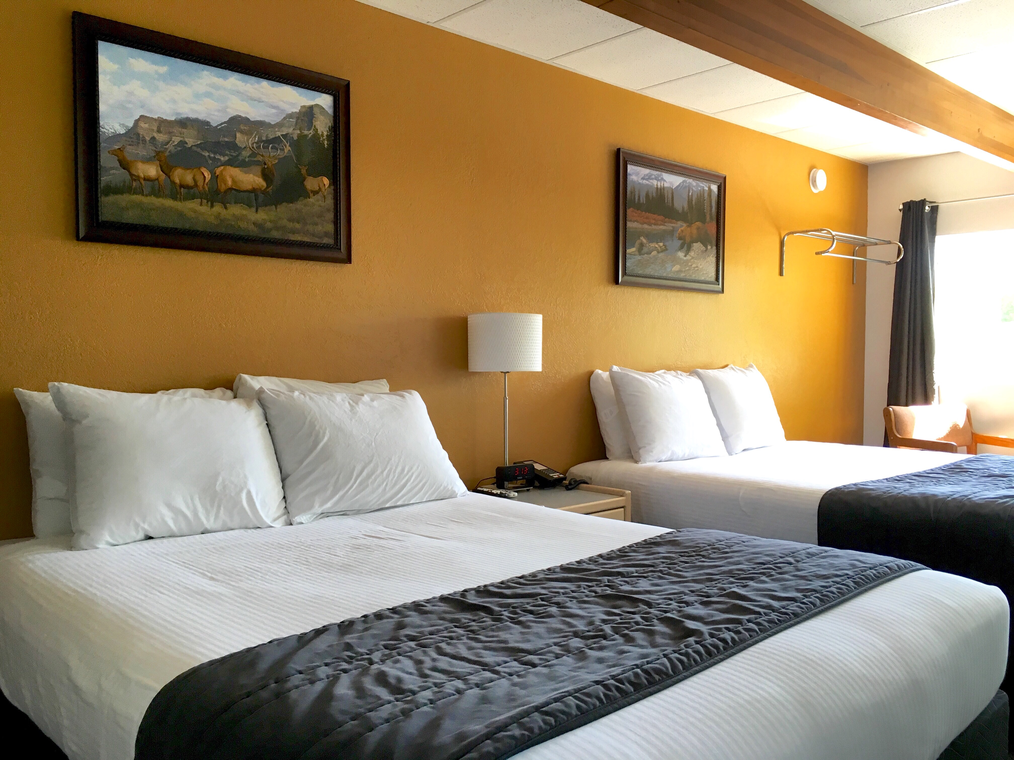 Our larger upstairs rooms overlooking downtown missoula and broadway street feature two queen beds a small table and chairs and a private bath with tub